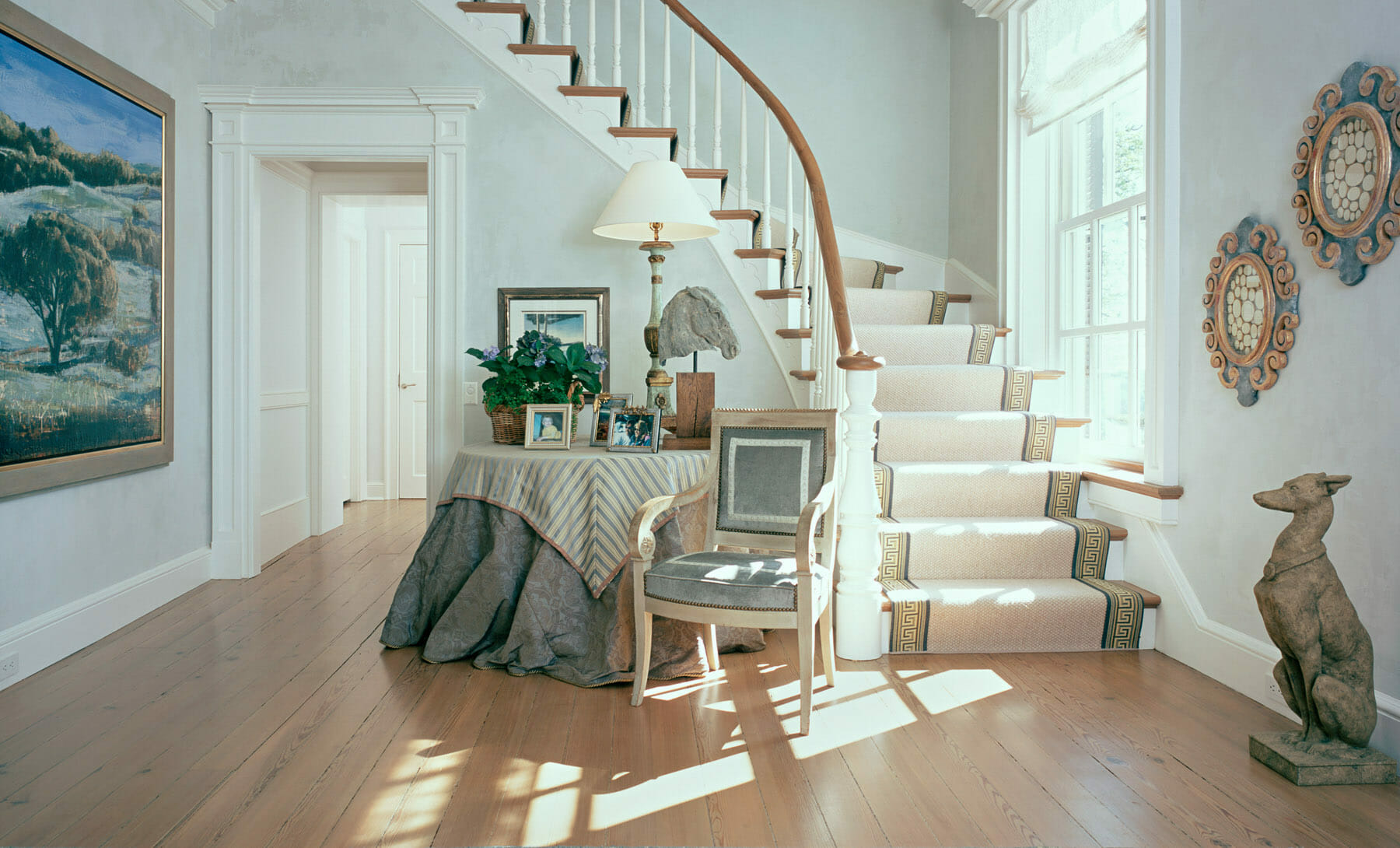 Winding staircase with wooden banister and wood floors with natural sunlight in Charlottesville, Virginia.