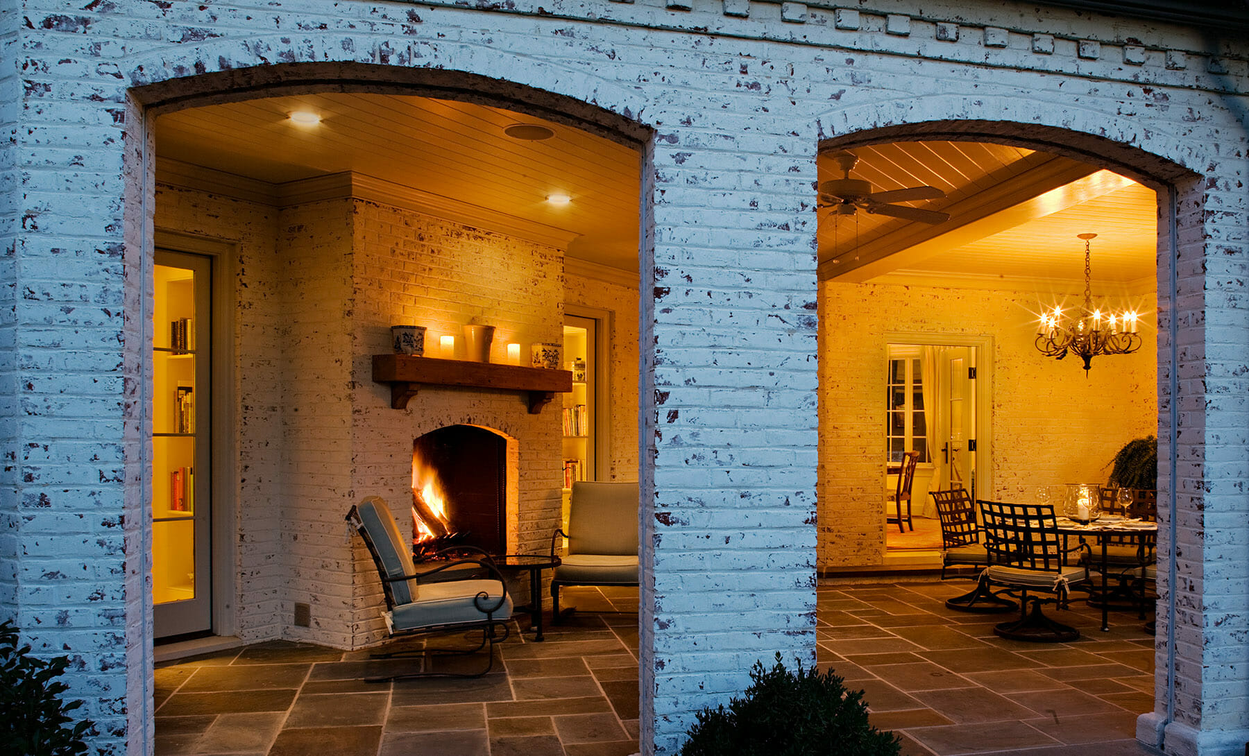 Covered patio with fireplace and nighttime lighting located in Charlottesville, Virginia and built by GME Builders