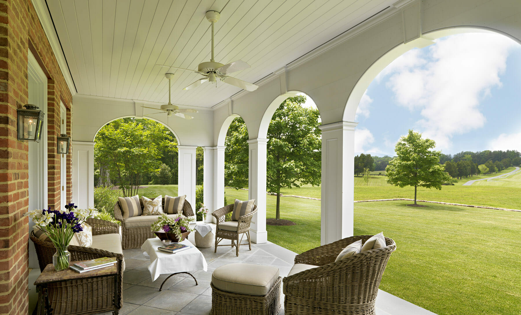 Covered veranda with outdoor fans and wicker chairs on an estate in Albemarle County, just outside of Charlottesville, Virginia. The veranda was built by GME Builders.